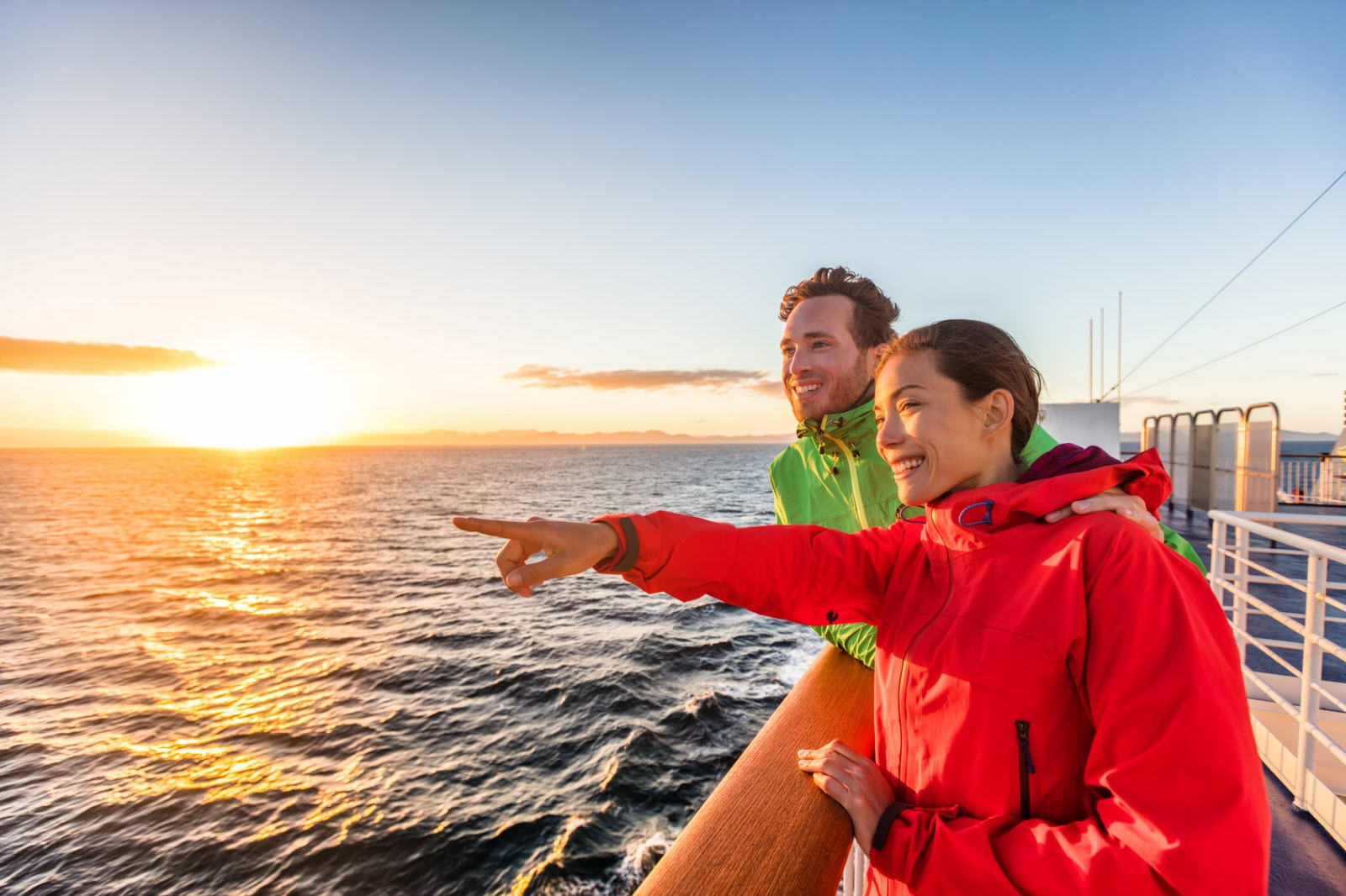 Cruise travel tourists couple pointing at sea view from ferry tour. Asian woman multiracial people traveling together at sunset.
