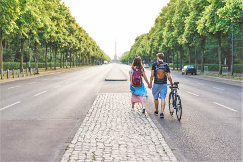rear view of couple of tourists with bicycle walking at street in berlin germany