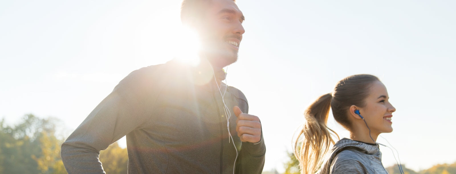 happy couple with earphones running outdoors