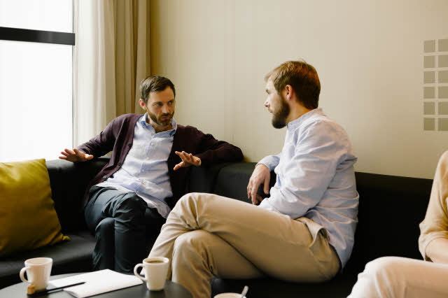 Two men discussing over coffee in sofa